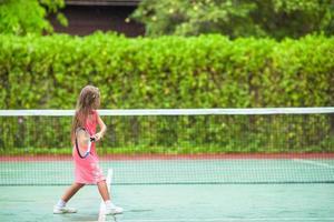 Mädchen, das Tennis im rosa Kleid spielt foto