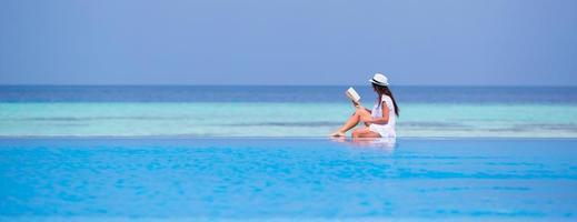 Frau, die ein Buch liest, während sie am Rand eines Schwimmbades sitzt