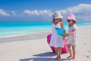 Mädchen gehen mit einem Koffer und einer Karte am Strand spazieren