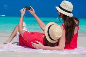 Paar, das ein Foto von sich am Strand macht
