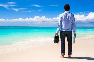Mann mit Laptop und Schuhen am Strand