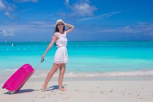 Frau, die mit ihrer Tasche auf einem tropischen Strand geht foto