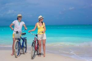 Paar zu Fuß mit Fahrrädern am weißen tropischen Strand
