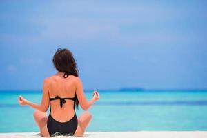 Frau meditiert an einem weißen Strand
