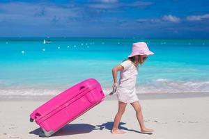 Mädchen mit rosa Koffer, der auf einem Strand geht foto