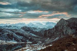 Berge mit schneebedeckten Gipfeln und Wolken bei Sonnenuntergang
