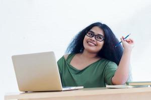 lächelnde Frau, die an ihrem Laptop arbeitet foto