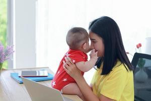 junge asiatische Mutter, die von zu Hause aus arbeitet