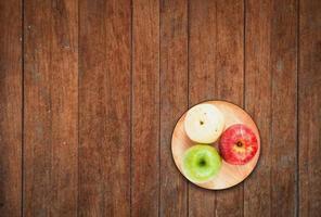 Draufsicht von drei Äpfeln auf einem hölzernen Hintergrund
