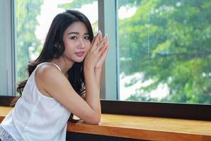 asiatische Frau, die durch ein Fenster aufwirft