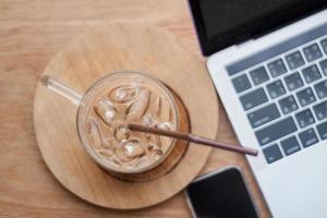 Eiskaffee neben einem Laptop und einem Telefon