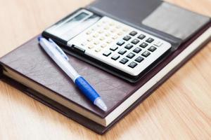Taschenrechner und Stift auf einem Notizbuch foto