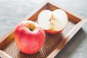 zwei rote Äpfel auf einem Holztablett