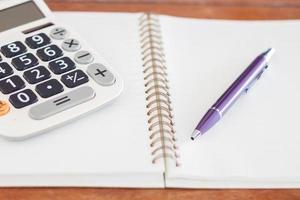 Taschenrechner und Stift auf einem Spiralblock foto