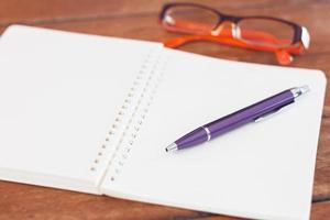 Öffnen Sie das Notizbuch mit Stift und Brille foto