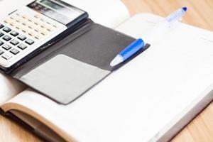 Taschenrechner mit einem Notizbuch und einem Stift foto