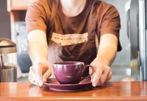 Barista bietet lila Tasse Kaffee foto