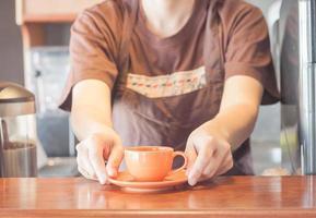 Barista bietet eine orangefarbene Kaffeetasse an foto