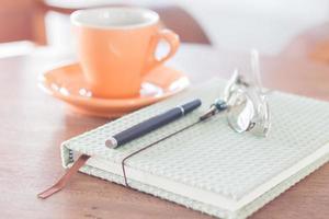 Notizbuch, Stift und Brille mit orangefarbener Kaffeetasse
