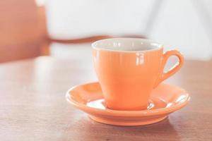 orange Tasse auf einem Holz fähig