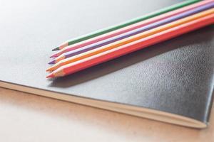 Nahaufnahme von Farbstiften auf einem schwarzen Notizbuch