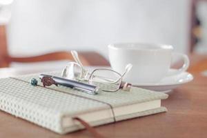 Notizbuch mit Stift, Brille und weißer Kaffeetasse