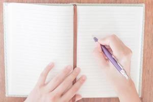 Frau schreibt in ihr Notizbuch foto