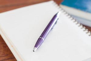 Nahaufnahme eines lila Stiftes auf einem Notizbuch foto