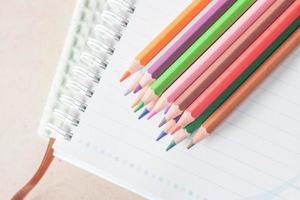 Draufsicht von bunten Stiften auf einem Spiralblock foto