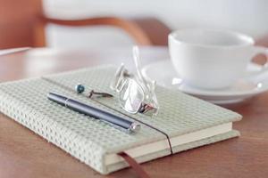 Notizbuch mit Stift und Brille