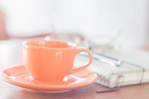 Mini orange Kaffeetasse mit einem Notizbuch