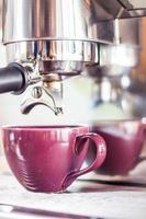 lila Tasse unter einem Espressotropfen