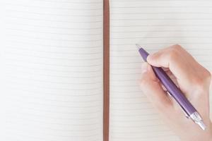 Nahaufnahme der Hand einer Frau, die auf ein Notizbuch schreibt foto