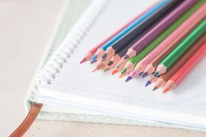 Nahaufnahme von bunten Stiften auf einem Notizbuch foto