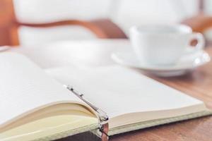 Öffnen Sie Notizbuch und Stift mit einer Tasse Kaffee