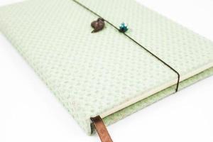grünes Notizbuch auf weißem Hintergrund