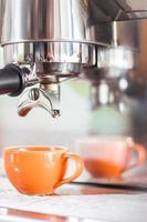einzelner Espresso in einer orangefarbenen Tasse