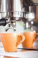 orange Espressotasse unter einem Espressotropfen