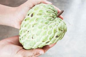 Person, die eine grüne Frucht hält