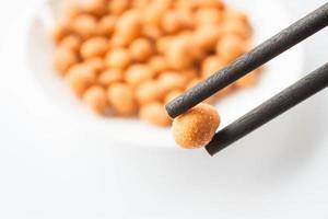 Nahaufnahme von würzigem Erdnusssnack und Stäbchen foto