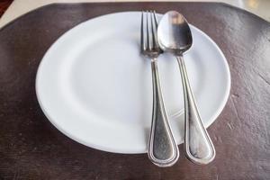 Draufsicht auf eine weiße Platte mit einem Löffel und einer Gabel