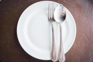 Draufsicht auf einen weißen Teller und Besteck