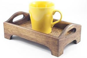 gelber Becher auf einem Holztablett foto