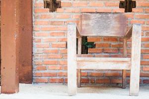Holzstuhl mit einer roten Backsteinmauer foto