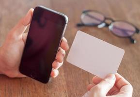 Person, die ein leeres Telefon und eine Visitenkarte hält foto