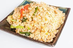 gebratener Reis mit gebratenem Schweinefleisch auf einem schwarzen Teller