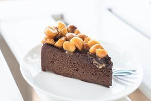 Macadamia-Schokoladenkuchen auf minimalem weißem Hintergrund foto