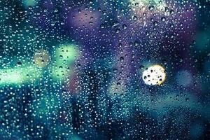 Regentropfen auf dem Fenster mit buntem Bokeh