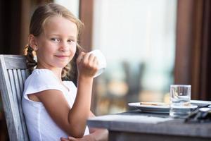 Mädchen trinkt Tee am Tisch foto