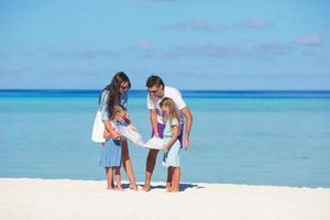 Familie, die eine Karte auf einem Strand betrachtet foto